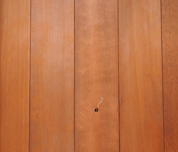 玄関ドア横には無垢材の羽目板。米杉の板張りで格好良く。